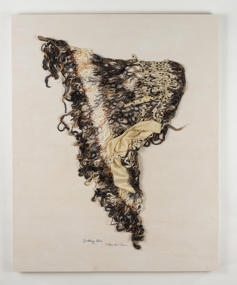 """Clothing Relic 1"""" is a fiber work of soft greys, browns, and ivory. Handknit of wool and chenille yarns and silk sari ribbon, it is mounted on a wood panel with overall dimensions of 30 x 24 x 1.5. This fiber creation is graceful and flowing in"""
