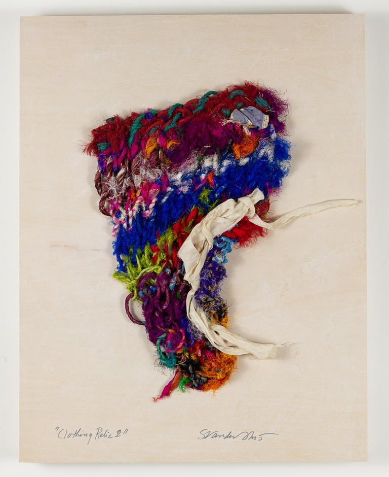 """Clothing Relic 2"" is a fiber work of predominately red, blue, and ivory. Handknit of silk sari ribbon, it is mounted on a wood panel with overall dimensions of 18 x 14 x 1.5. This fiber creation is highly textured and bold. Artist signature is on"