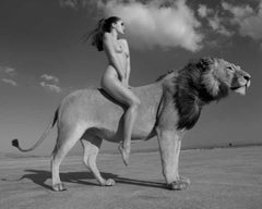 Angela rides the lion -  portrait of a female nude riding a lion in the desert