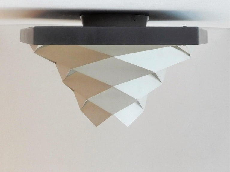 This decorative flushmount is a modernist and quite rare design by Preben Dal for Hans Følsgaard. A design from the early 1960s made of white and dark grey steel elements. The shape of this lamp gives a fantastic light, a true eyecatcher! We have 2