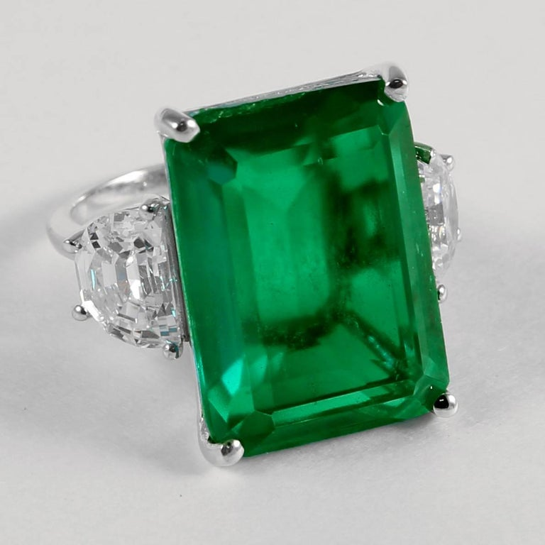 Magnificent Costume Jewelry  Amazing faux 25 carat rectangular step cut man-made emerald made of the finest green  natural material faux emerald set with half moons either side in white gold. This ring has an amazing warm glow. Measures 1inch long