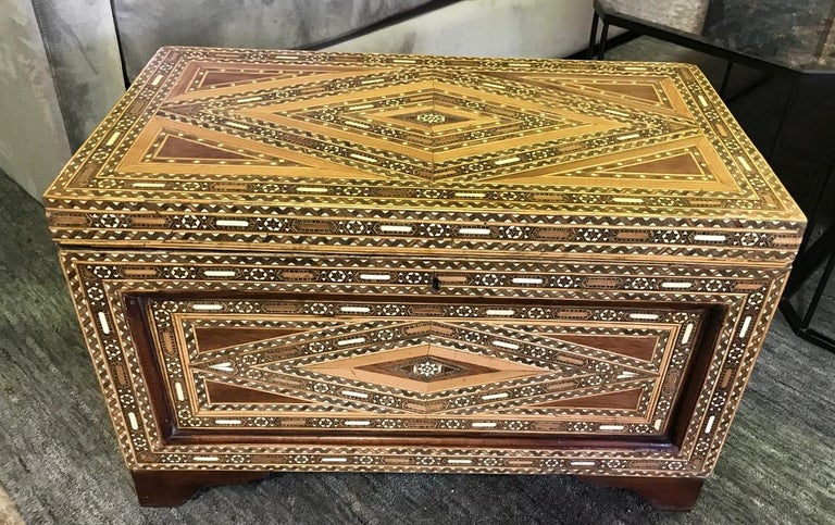 Stunning mosaic, geometrical design and gorgeous craftsmanship. The trunk is made of various wood, mother of pearl and bone inlays. A genuine work of art.   Would stand out in any setting or home.   Please note that at one time the piece may