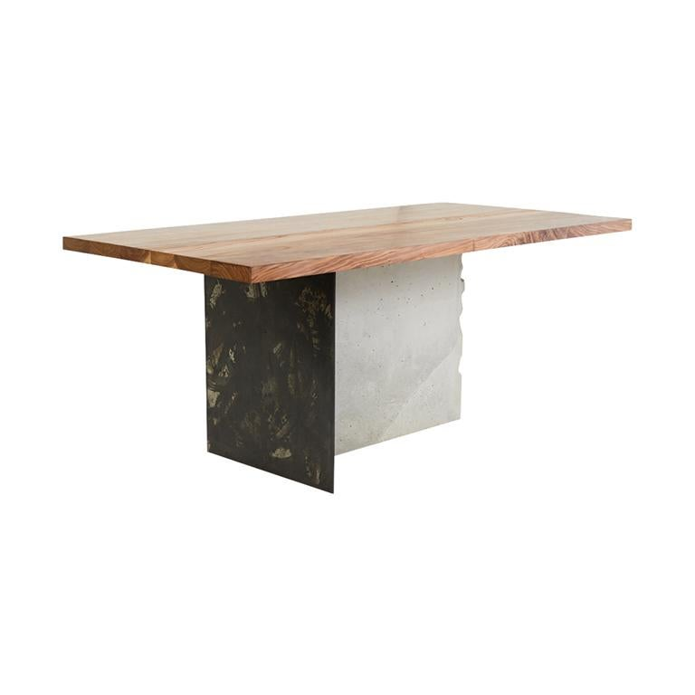A solid walnut wood top rests on a base composed of Stefan Rurak Studio's unique patinated steel, joined with concrete. The leg is cast and then cracked by hand, revealing the rebar within. An abstract line drawing is etched into the Walnut top