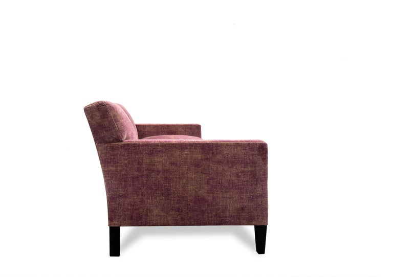 The T-Back sofa has a tight upholstered back and loose seat cushions. Tapered front legs and squared back legs are made of blackened hardwood. Upholstered in a vintage effect cotton velvet textile.