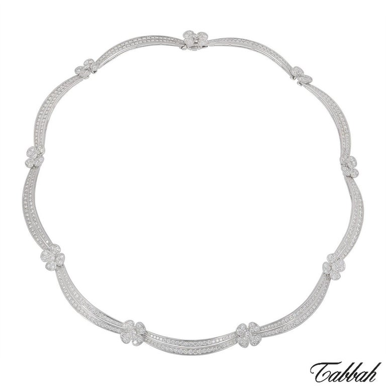 An 18k white gold jewellery suite by Tabbah. The suite is composed of a floral necklace pave set with round brilliant cut diamonds which has 9 flower motifs joined up by a diamond set 2 bar row, the earrings feature a pave set flower motif set with