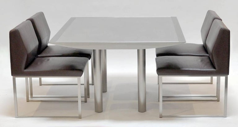 Outstanding table and chairs. Designed by Stanley Jay Friedman for Brueton. The table features a polished steel apron with an orbital grain patterned steel top. The legs are 3