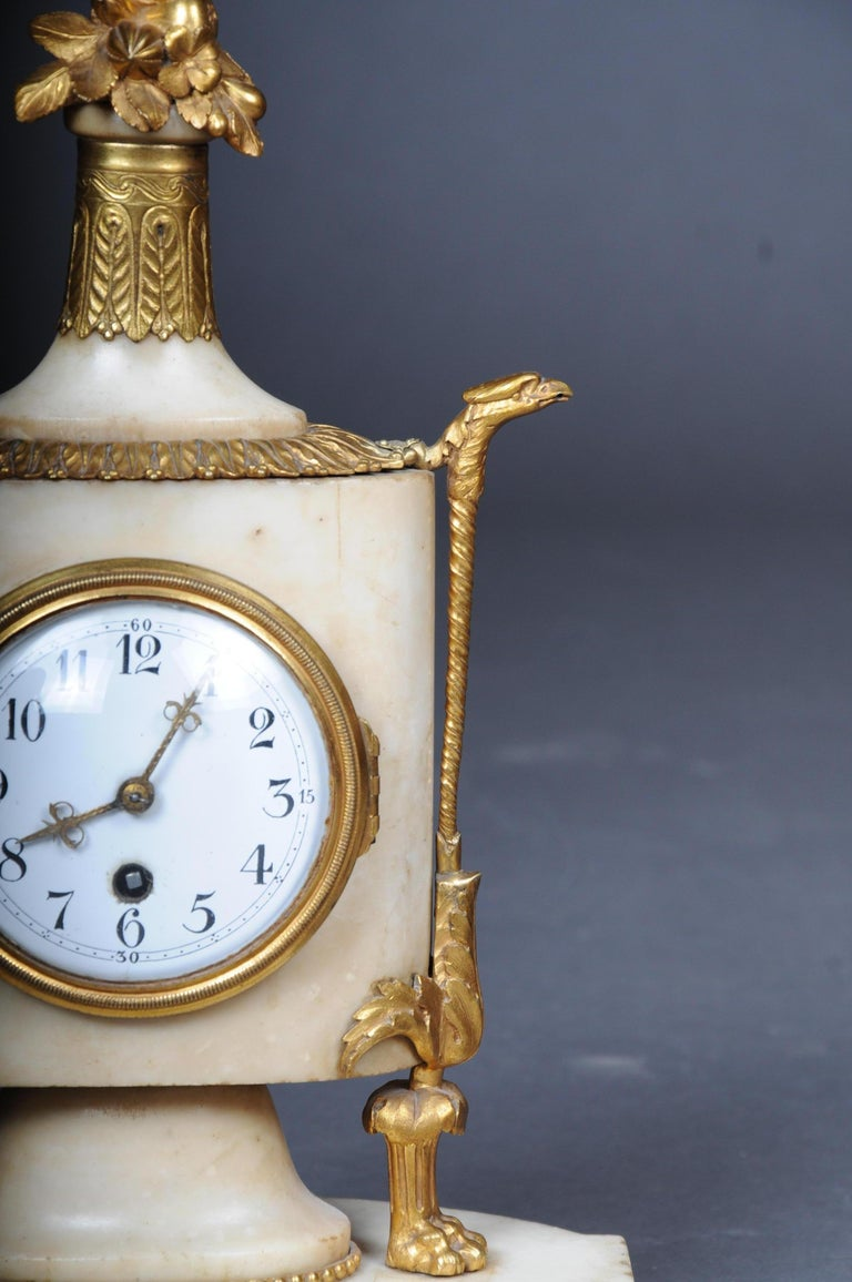 Table clock / fireplace clock in Empire style around 1900 White marble, bronze, gilded. On four roundel base oblong base plate and the oval in cross-section watch case, flanked by slender spiral supports on paw foot and eagle head ending. Glazed