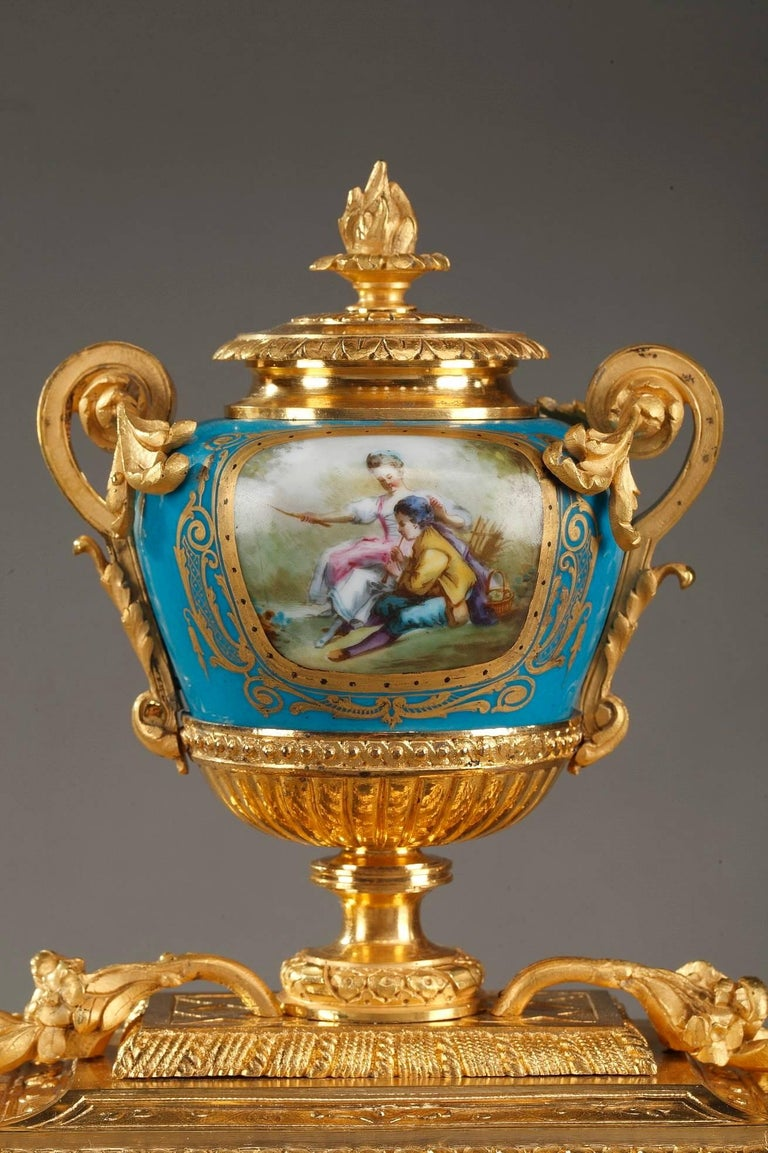 Gilt bronze antique table clock decorated with polychromatic porcelain panels. Telling the hour on Roman numerals, the timepiece features a blue and white enamel dial, painted with a gallant scene in 18th century taste. The sides are decorated with
