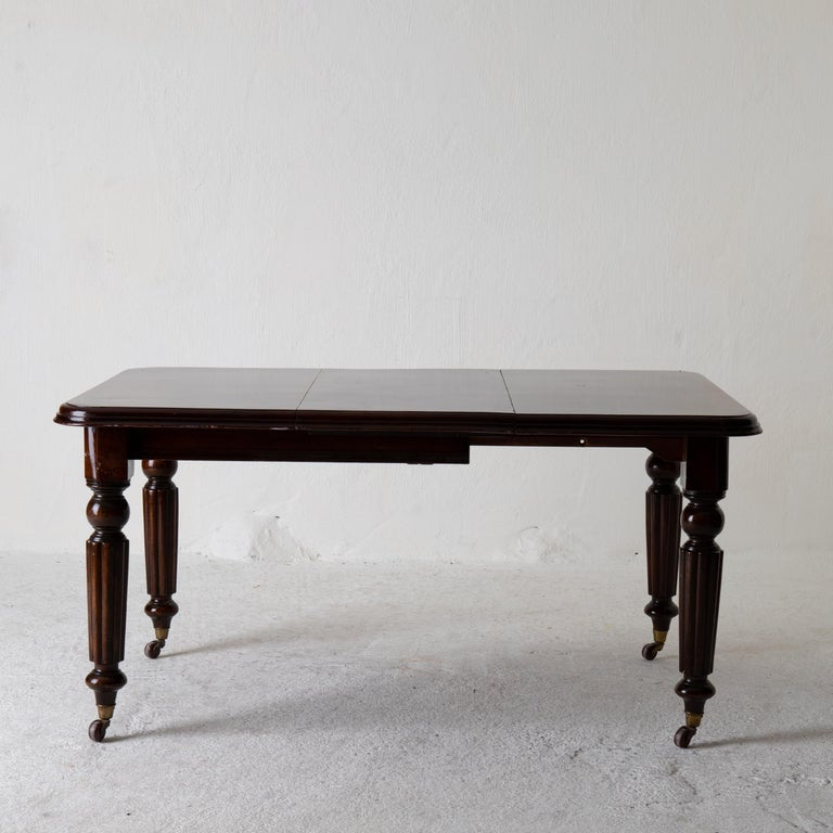Table dining table English dark brown mahogany 19th century England. A table made during the 19th century in England. Made in dark mahogany. Extendable top with one leaf and rounded corners. Round and channeled legs standing on brass casters. Leaf:
