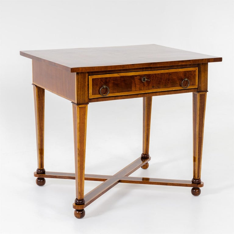 Table with wide drawer and ring-shaped pull handles. The tapered legs rest on ball feet with x-shaped bracing. The tabletop with beautiful inlays.