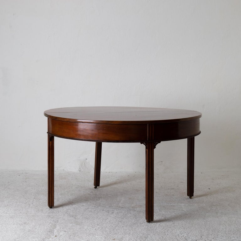 Table game table Gustavian Swedish demilune mahogany brown, Sweden. A game table made during the Gustavian period in Sweden. Veneered in a dark brown mahogany and decorated with a pearl beading and reeded legs. Demilune shape that opens up to a full