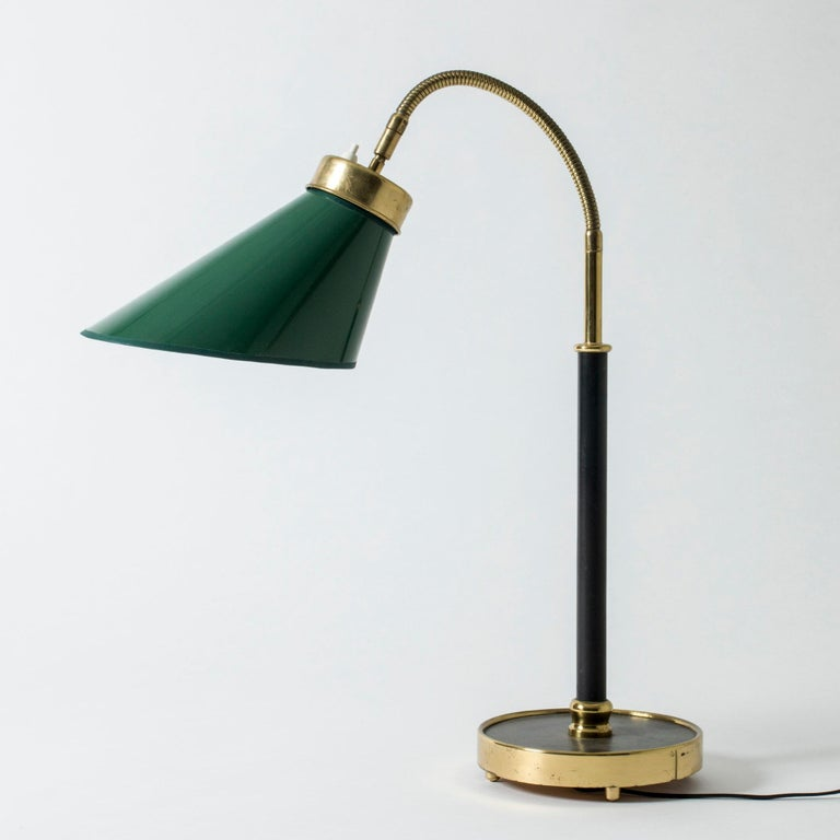 Very rare, elegant brass table or desk lamp by Josef Frank, with a dark green shade. Original black leather upholstery on the stem and base. Flexible neck and decorative round brass feet.