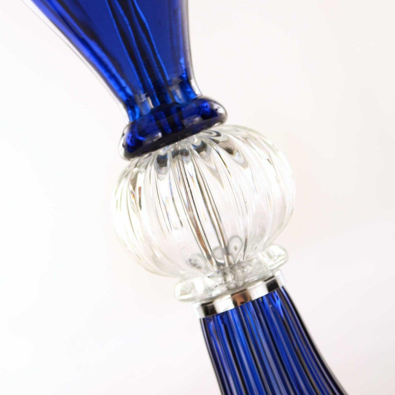 This table lamp is in artistic blue and transparent Murano glass, the lampshade is in white cotton with blue trimmings.