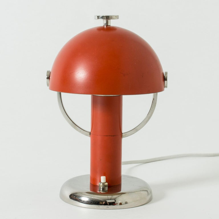 Gorgeous little table lamp by Bo Notini in a very functionalist design. The shade can be adjusted in various angles. Cool metal details against the red lacquer.