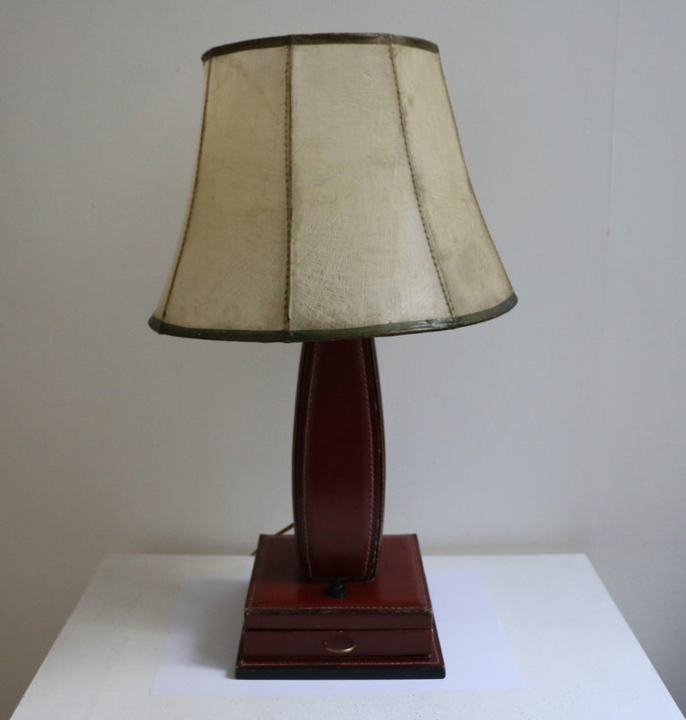 Table lamp by Jacques Adnet with red stitched leather entirely covering a wood structure. Square base with a small drawer (brass handle). Shade is original and made fiberglass on metal thread. Wired for European use.