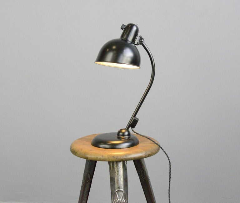 Table lamp by Kaiser Jdell, circa 1930s  - Steel shade with relief Kaiser Jdell branding - On/Off switch on the base - Takes E27 fitting bulbs - Adjustable arm and shade - Designed by Christian Dell - German ~ 1930s - Measures: 46cm tall x