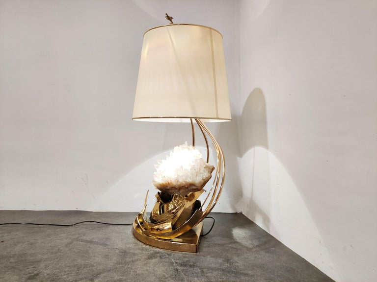 Impressive hand made table lamp with a big piece of rock crystal showcased on a etched brass base and sculpted leafs.  The table lamp is signed on the base.  It creates a beautiful light effect.  A true statement piece and beautiful piece of