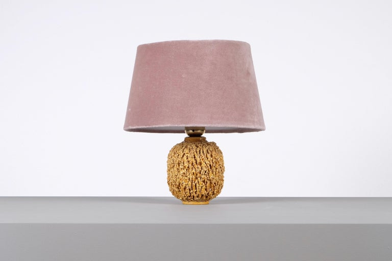 Ceramic lamp in bulbous shape by Gunnar Nylund, composed of chamotte clay and glazed with a gold colored luster glaze. Produced by Rörstrand.  Stamped. Height including shade: 28 cm. New wiring.