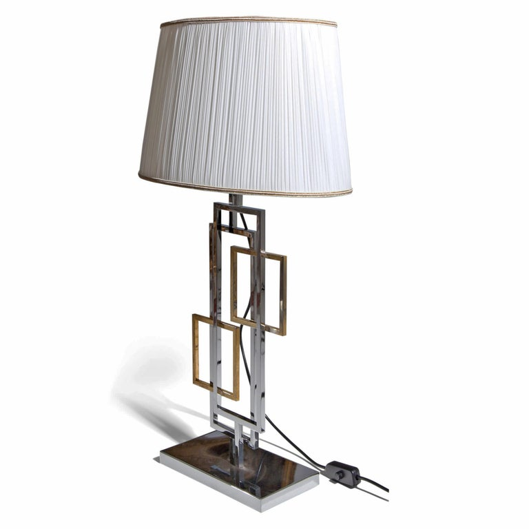 Italian Lamp in the style of Romeo Rega standing on a rectangular chrome foot with geometrical forms out of brass and metal and a beige lamp shade (recent).   For the electrification we assume no liability and no warranty.