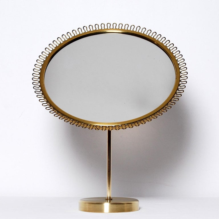 Table vanity mirror designed by Josef Frank produced by Firma Svenskt Tenn during the 1950s. Brass with a teak back. Adjustable angle.