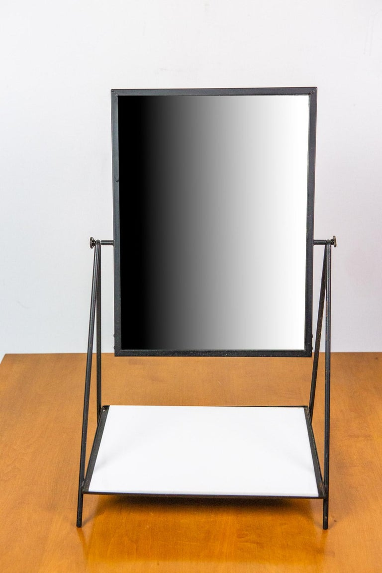 Elegant table mirror, designed by Paul McCobb, is constructed of a painted metal frame with a swiveling mirror and a white glass shelf. Turns any surface into a functional vanity. The white glass shelf offers a raised platform for storage or display.