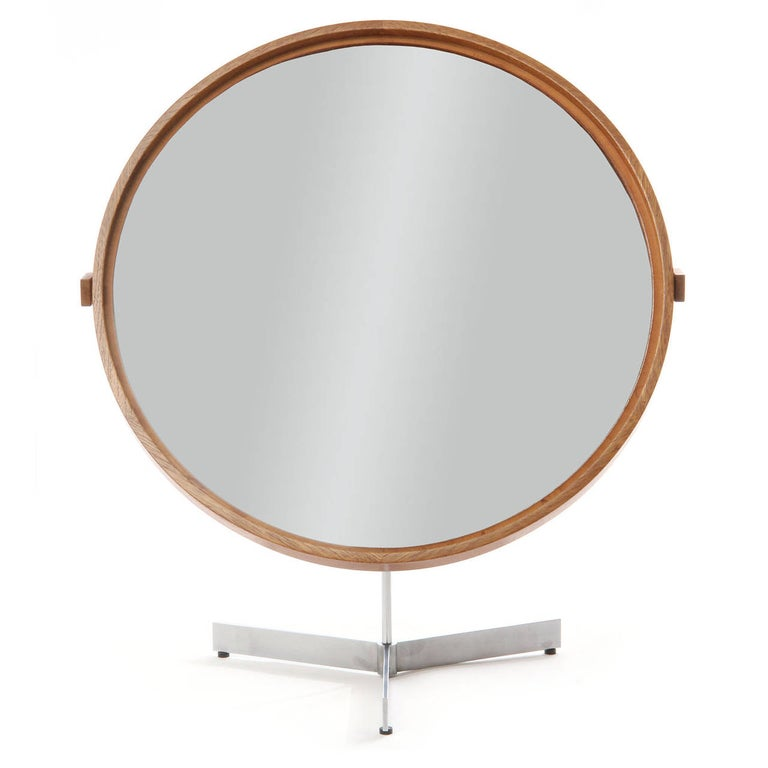 A Scandinavian Modern vanity mirror featuring an elegant tilting and swiveling oak framed that floats on an architectural brushed steel tripod base. Crafted by Luxus in Sweden, circa 1960s.