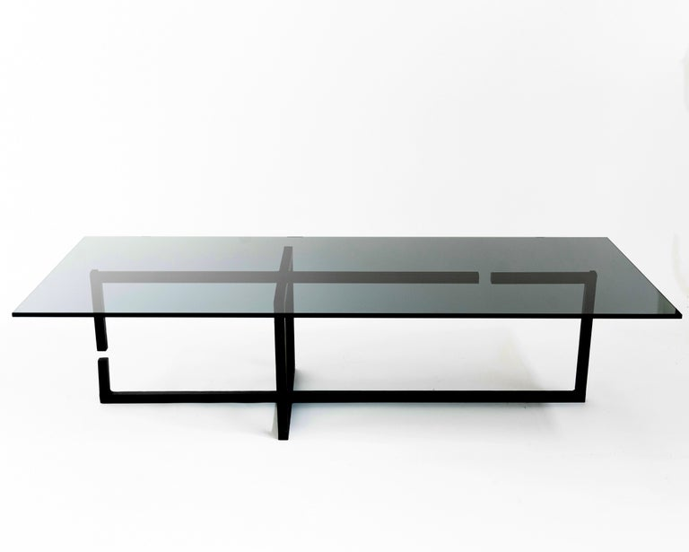 """Table No. 6 by JM Szymanski Dimensions: L 60"""" x W 26"""" x H 15""""  Materials: Blackened waxed steel, glass  This abstract frame supports a 3/4"""