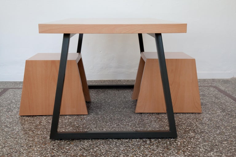 Table with metal base made of MDF lined beechwood. The base is bent, galvanised metal, oven-painted with acrylic grey color.