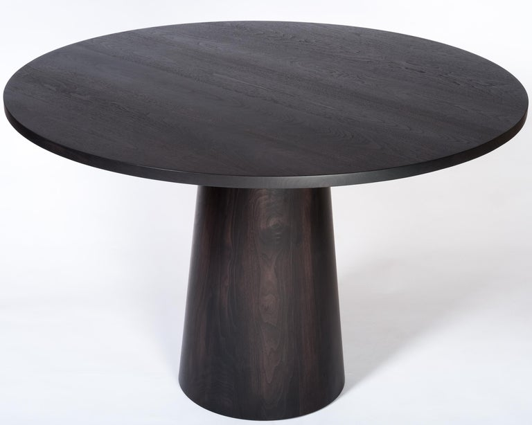 An elegant round dining table with a solid wood base and top. Photos show the table in an oxidized walnut finish which turns the table to a near black yet still allows the beautiful grain and warmth of walnut to come through. Also available in