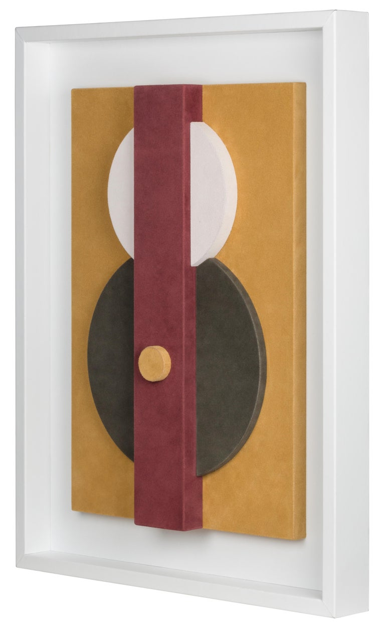 This suede-covered wall sculpture is framed in white nappa.