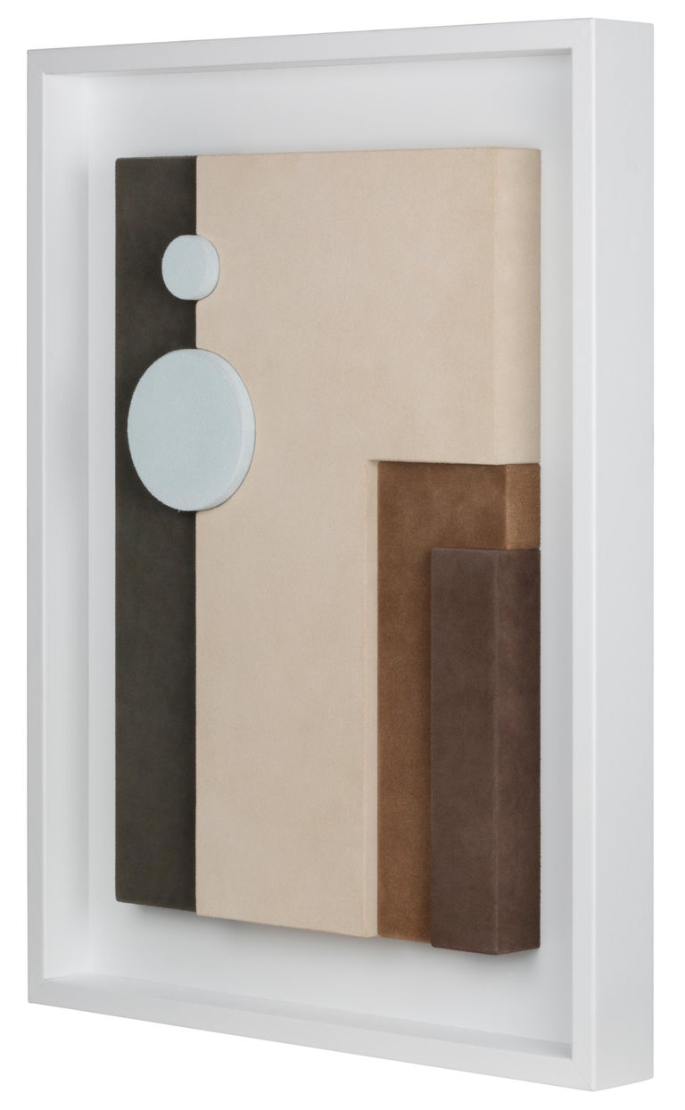 This suede-covered wall sculpture is framed in white nappa. The interaction between colors and shapes makes it a decorative piece based on pure geometry, where abstraction and figuration create formal structures that allow colour to dominate. This