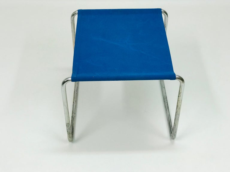 The tabouret by Marcel Breuer is in original condition. The fabric seat is attached with steel chrome-plated construction.