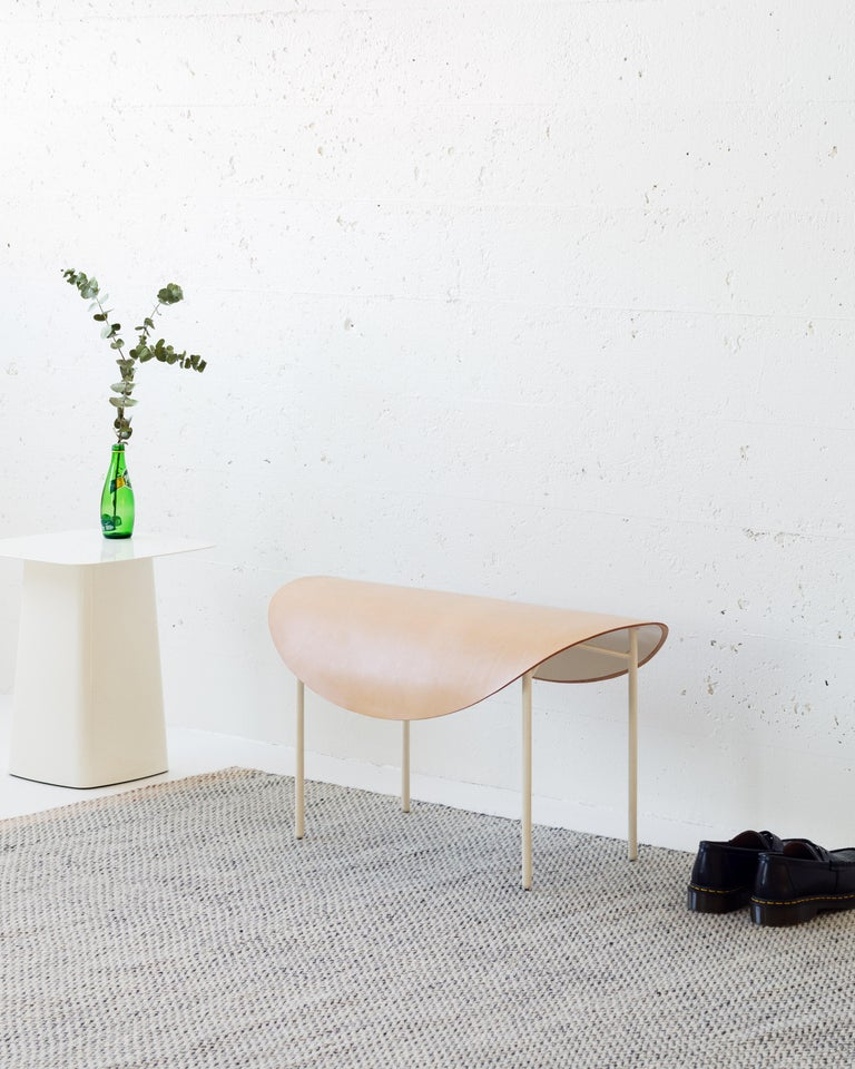 The tack bench takes its form from equestrian accoutrement. The seat is a curved steel surface softened by a thick vegetable tan leather oval with a nod to the shape of a saddle. The curved seat drapes over four slender steel legs with non marking