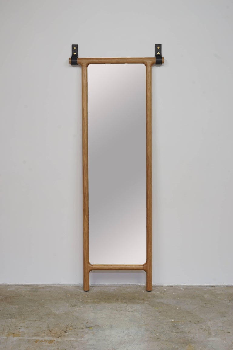 Leaning floor mirror with thick leather straps that help keep it upright.