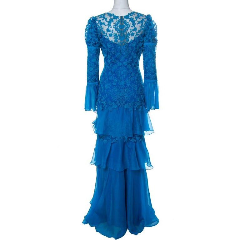 Tadashi Shoji designs elegant evening wears with subtle hints of glamour. This blue gown comes in tulle with long sleeves, embroidery and a tiered design. Exuding feminine charm, you can team this evening gown with elegant heels and accessories to