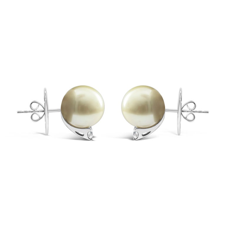 Simple stud earrings showcasing two 11.90 millimeter Tahitian pearls accented by a single round diamond. Diamonds weigh 0.31 carats total. Made in 18 karat white gold.