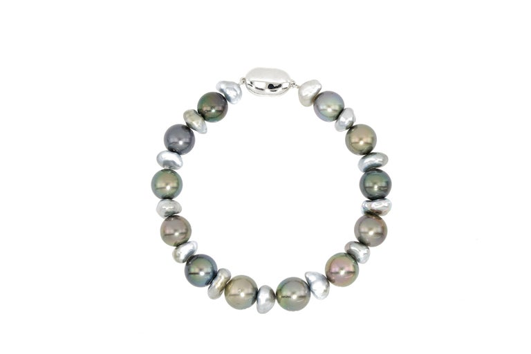 A very beautiful  pearl bracelet with 25 pieces of natural colour Tahitian pearls, from 8mm to 11mm in diameter, with 12 pieces being round, smooth and of very good luster, the other 13 pieces being irregular shaped keshi pearls in silvery grayish