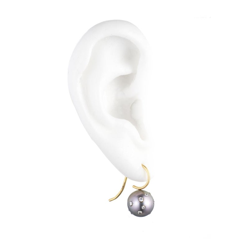 Pair of silvery grey Tahitian cultured pearl sprinkled with diamonds, suspended from 18K gold ear wires. The diamonds are scattered like confetti around the pearls. It's a charming touch.  Each pair is unique.  Description: Each Tahitian cultured