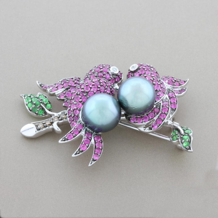 These two ruby studded love birds resting a branch of fancy color diamonds with emerald leaves and a pair of perfectly rounded lustrous Tahitian pearls will melt your heart. Set in 14K white gold and ready to be worn.  Brooch Length: 1.75