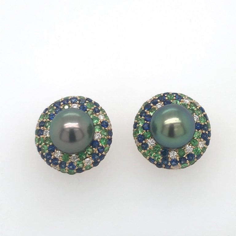 18K Yellow Gold earrings featuring two Tahitian pearls measuring 10-11 mm flanked with diamonds, 0.42 carats, blue sapphires, 1.95 carats and green tsavorite, 1.50 carats.