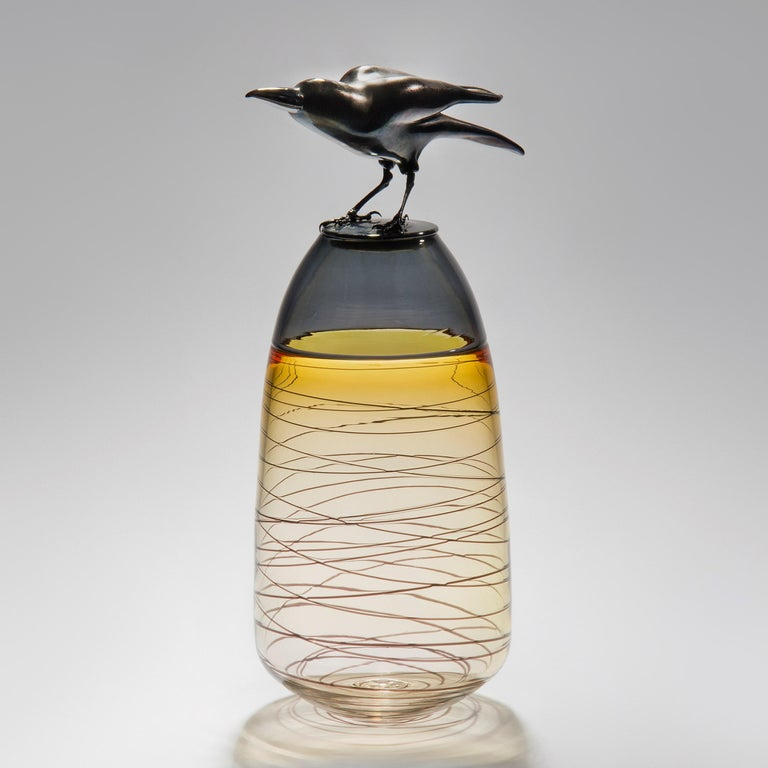 Take Off, is a handblown art glass vase in amber with removal lid adorned with a hot sculpted black glass crow by the British artist Julie Johnson. The crow figurine can also be lifted off with the main body leaving a functioning vase.  Following on