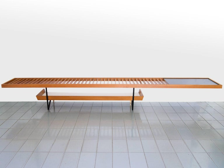 Huge table or bench made of vertical Pau Marfim slats, with magazine holder underneath and a formica top table to the right side. This piece is unique and made to order in 1958. It should be fixed to the walls in the back and on the right side