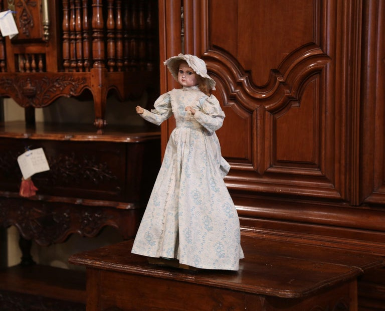 Here is a treasure for doll collector! This 19th century doll by Jumeau was crafted in France, circa 1870; the doll's head and right arm are in motion when the music is been played by cranking the knob on the base. The head and hands are made of