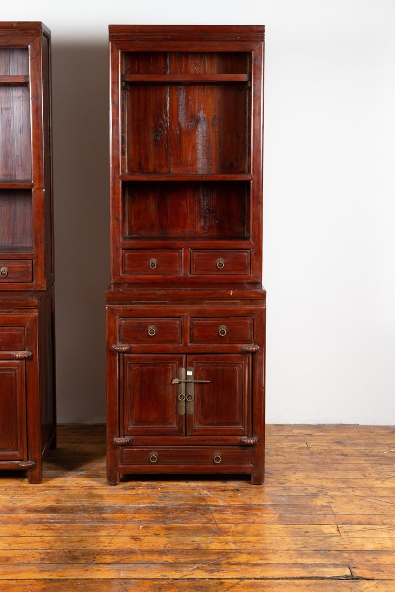 A tall Chinese antique two-part wooden lacquered cabinet from the early 20th century, with open shelves, doors and drawers, perfect to work as a pair with its twin (see item LU863916021382). Born in China during the early years of the 20th century,