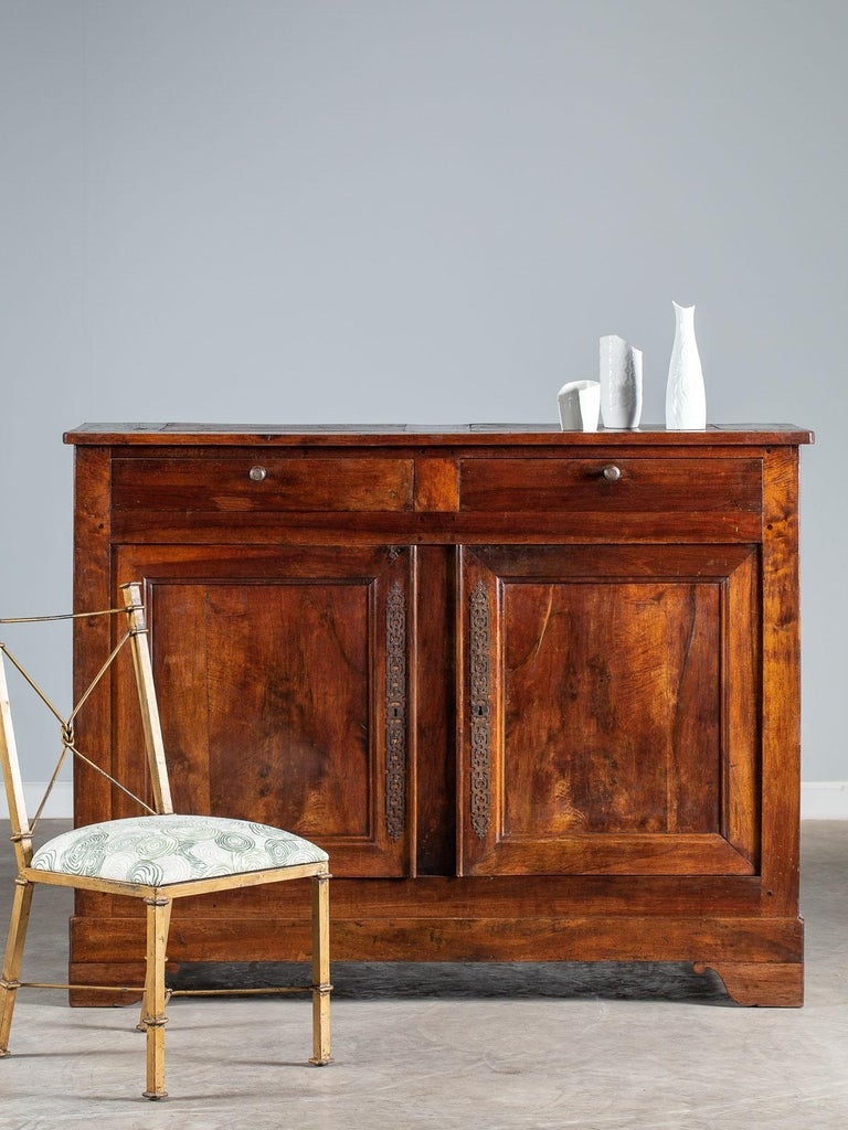 A tall antique French walnut buffet credenza circa 1820 having two drawers above two cabinet doors. The luscious walnut timber with its beautiful grain is visible across all the surfaces where the highly waxed and polished patina enhances the depth