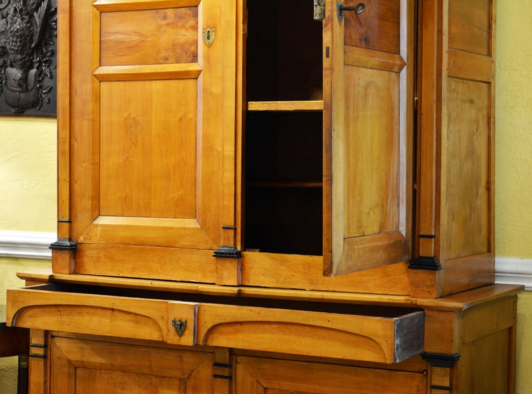 This buffet consists of an upper and a lower part. The upper part is surmounted by a wide shaped cornice and features two paneled doors opening up to a shelved interior. The lower part features a long drawer above two doors opening up to a shelved