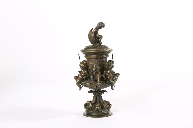 Early 20th century tall bronze non removable covered urn / centerpiece. The centerpiece is in great condition. It measures about 21 inches high x 14 inches wide.