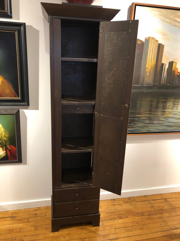 This is a totally functional tall one door cupboard with two exterior drawers and one hidden drawer. It is created from naturally rusted, salvaged and recycled ship building steel. Inspired by the Shaker aesthetic, this piece is all about clean