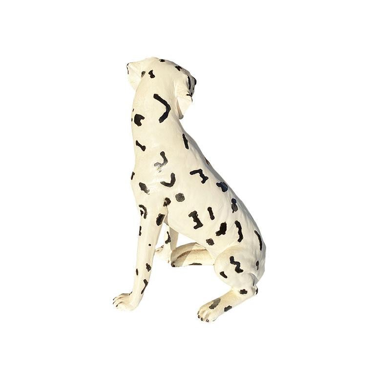 A gorgeous classic Dalmatian dog statue in black and white. This beautiful hand-painted canine is created from ceramic, and hand-painted in black and white. He sits on his loins and has floppy spotted ears. He has piercing yellow eyes created from