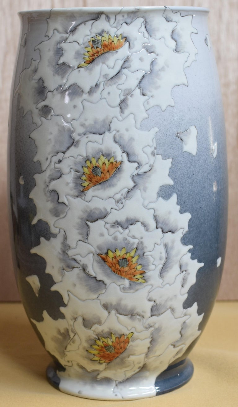 Exceptional Japanese contemporary decorative tall Kutani porcelain vase, hand painted in a white color on a blue/gray gradation. It is a masterpiece by a Kutani master artist whose signature bald flowers create a breathtaking scene.